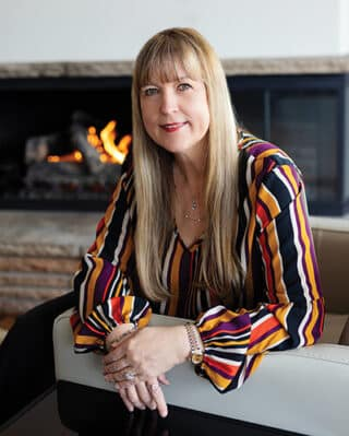 Portrait of Angela Sinickas Shiromani sitting in front of a fireplace wearing a colorful striped shirt